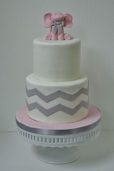 A beautiful cake or tiered platter of mini cupcakes (more practical than larger ones) is highlight of dessert table -- Can make or break entire table -- Needs to be special.  pink & grey baby shower ideas | tier pink elephant baby shower cake with gray chevron accent