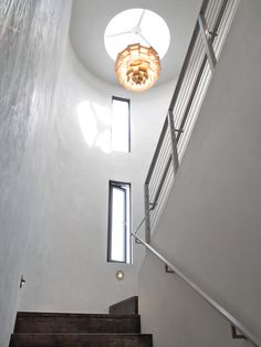Crowning the interior hallway is a Louis Poulsen PH Artichoke pendant, designed in 1958. The narrow apertures were designed to funnel the ocean breeze, contributing to the home's passive cooling program. The walls are covered in American Clay, which helps to control humidity.