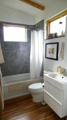 "SkimStone on the shower walls. ""We'd never seen it used on a shower before (just countertops), but it's really easy to use. It goes on like joint compound and looks like polished concrete. I did two coats of SkimStone and then 10 coats of a concrete water sealer. Very inexpensive and easy!"" - owner/designer"