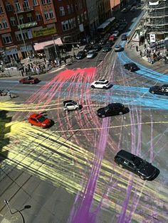 A group of cyclists dumped 13 gallons of paint on the road at Berlin's busy Rosenthaler Platz, creating a series of colorful lines as cars drove through. So the cars and their wheels, if the driver wanted it or not, became the brush tool for this guerilla public art piece.