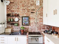 Rustic-Exposed-Brick-Wall-Accents-in-the-Minimalist-Kitchen-Design-Featuring-Large-White-Cabinetry-and-Simple-Black-Rack-for-the-Cups-and-Tiny-Green-Plants-Decoration