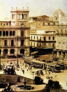 Imagen tomada hacia el sur de la Plaza del Zócalo, se observa la plancha con Jardinera y fuentes.  También la estación de tranvias. A la izquierda se observa el antiguo Palacio del Ayuntamiento y a la derecha lo que hoy es el Gran Hotel de la Ciudad de México. Año de 1925