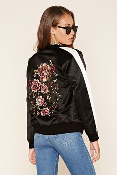 A woven bomber jacket featuring a floral embroidery on the back, zipper front, long striped sleeves, front slanted pockets, and ribbed knit trim.