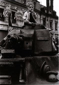 Robert Capa,   Paris 26 August 1944. French tank recaptured from the Germans. I love the finger up the nose! :)