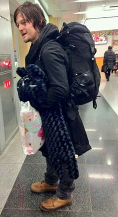 Norman Reedus carrying a Hello Kitty bag and a big stuffed black cat!