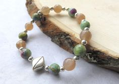 Ruby Zoisite and Peach Moonstone Bracelet  ||  This bracelet is a unique design using both moonstone and ruby zoisite gemstone beads. The greens and peach tones are stunning coupled with the sterling silver  https://jemsbyjbandcompany.com/products/moonstone-and-ruby-zoisite-gemstone-bracelet-silver-and-green-stone-bracelet-gemstone-stretch-bracelet-modern-moonstone-gift-for-her?utm_campaign=crowdfire&utm_content=crowdfire&utm_medium=social&utm_source=pinterest