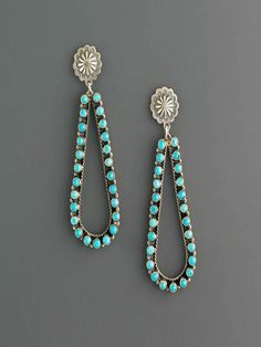 Teardrop cluster earrings set with Sleeping Beauty Turquoise and fastened with a small stamped silver charm stud. Via Don Lucas