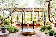 Outdoor dining space with a rustic water feature and trees