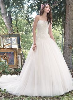 Becca wedding dress by Maggie Sottero   A fitted lace bodice, accented with a stunning illusion sweetheart neckline flowing into a voluminous tulle skirt in this enchanting ball gown wedding dress. Finished with corset closure.