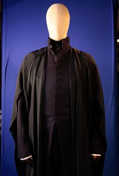 """As the Head of the Slytherin house, Snape's costume served to make him look long and thin, like a snake. Alan Rickman was dressed from head to toe in very dark navy to indicate his role as a villain. The clothes are reminiscent of a 19th century gentleman, with a high collared, Melton wool, frock coat and narrow legged trousers."""