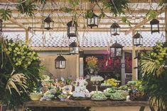 Mesa de doces rústica, elegante, com mesa de madeira, colorida e lanternas penduradas. Decoração de Kátia Criscuolo em Trancoso