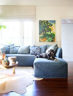 Blue L-shaped sofa in living room with small dog, forest art, and styled coffee table