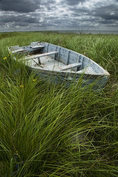 old weathered row boat abandoned in a field of grass