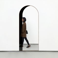 Arch Floor Mirror  The Arch Mirror brings one of the most ancient, classic architectural elements into any room. In addition, the effect of this mirror is strikingly realistic, seemingly opening a window or doorway through the wall, magically creating an opening into another space. Materials: Black and Clear Mirror, Walnut Frame