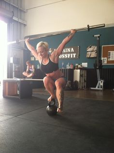 This woman is doing an overhead pistol squat on a kettlebell. If you've never done a pistol squat, or an overhead squat, I want you to know that this is insanely difficult. #crossfit