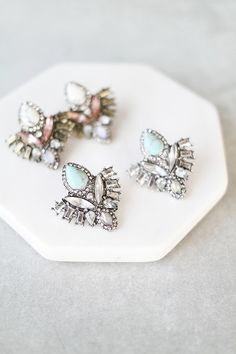 """Crystals and stones set in silver or gold on stud earrings. Details: - 1.25"""" drop - 1"""" wide - Post back"""
