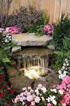 Wasserspiele im Garten umgeben von blühenden Pflanzen