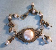 A Touch of Steampunk Vintage Faux Mabe Pearl Cabochon, Crystal and Antiqued Brass Charm Bracelet