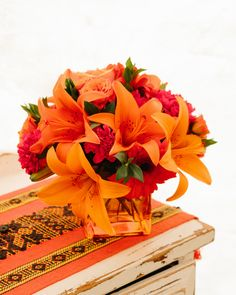 Orange gerbera daisies, orange roses and red mini carnations are accented with a spray of red huckleberry in an orange cube vase. Fall Flowers, Summer Flowers, Mini Carnations, Fall Bouquets, Orange Roses, Gerbera, Teleflora Flowers, Flower Arrangements, Daisy