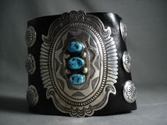 """The huge ornate 3"""" x 2-1/2"""" domed silver shield is the entire width of this black leather bowguard that does measure 8-1/2"""" long with leather tie for adjustability. The shield has a heart of vibrant triple turquoise stones, separated with dual silver beads. 