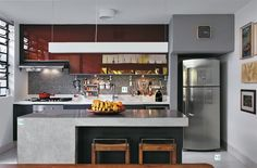 """10. O balcão de concreto de 0,90 cm de altura abriga a um só tempo o microondas, os bancos, duas portas de uma despensa estreita e uma porta de armário. 11. Ao fundo, a bancada da pia foi refeita com Corian (DuPont) e a parede revestida com mosaico de vidro (Vidrotil cor 730). 12. O piso de granilite dá um ar antiguinho e facilita a limpeza. """"Eu gosto cada vez mais desses materiais antigos que exigem pouco e resistem ao tempo"""", observa Maristela."""