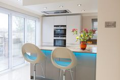 Blue LED lighting adds a surprising dimension to this otherwise toned down kitchen