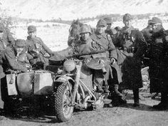 Soldiers posing with a dispatch rider on his Zundapp KS 750 during winter conditions