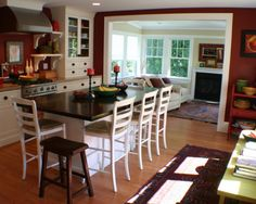 White cabinets and island with rich paint tones and hardwood floors