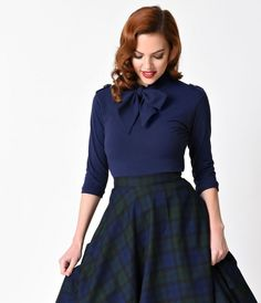 Vintage is for lovers, gals! A beautiful navy blue top, this 1940s jewel is prim and elegant, crafted in a soft stretch cotton knit. A high collar is dramatically embellished with a self tie bow and lovely white buttons on the shoulders for a charming ret