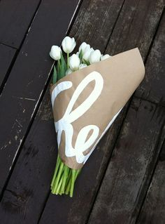 Kraft paper wrapped bouquet personalized with recipients name or sentiment painted/written in white.