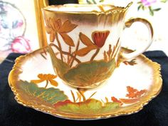 OFFERING THIS PRETTY JUST FANTASTIC TEA CUP AND SAUCER THIS WAS MADE IN ENGLAND 1890S SUPER DESIGN AND PATTERN NICE TEACUP WITH TRIMS OF THICK GOLD GILT AND PAINTED DESIGN NICE WATER LILY PATTERN ALL 24KT GOLD AND SCALLOPED TOOTH EDGES LIKE A CRIMPED PIE SHELL , FINE BONE CHINA WITH