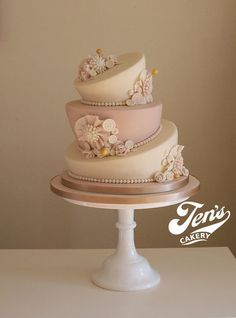 A very classy pink and beige topsy-turvy wedding cake with sugar flowers.    Sophie