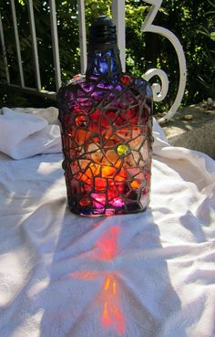 bottle painted with glass paint, mosaiced in clear glass and grouted in dark gray....and some bright glass stones for bling - Frances Green