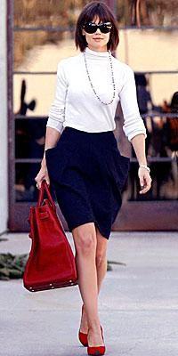 Katie Holmes in a black skirt, white turtle neck & a red Birkin.