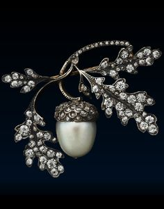 An antique diamond and Pearl Oak Leaf Brooch by René Lalique, circa 1880. Designed as a spray of oak leaves framing a natural bouton-shaped pearl and diamond-capped acorn, mounted in silver and yellow gold, French control marks stamped to the pin, and with an applied plaque stamped with the initials 'RL' for René Lalique. #Lalique #antique #brooch
