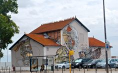 A collaboration of the Portuguese artist Vhils and Pixel Pancho on a building beside the Tagus river in Lisbon,