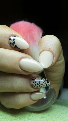 Beige nails with rhinestones and black arabesques