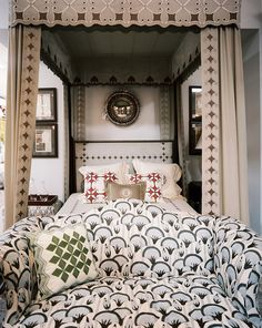 Furniture Photo - A patterned settee at the foot of a canopy bed