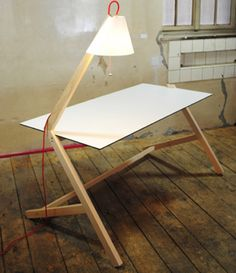 Table & Lamp par Florian Kallus  Table & Lamp est un ensemble, comme son nom l'indique, d'une table de travail et d'une lampe qui vient dans le prolongement de l'un des pieds. Le bras articulé de la lampe permet de choisir l'endroit à éclairer principalement. Ce produit est simple, minimaliste et efficace. Le fil rouge de la lampe n'est pas sans rappeler celui de la lampe de Nicolo Taliani.
