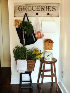 This antique-inspired sign is a practical and eye-catching accessory perfect for this small kitchen wall. Beneath the sign, two wooden stools serve as staging area for recently-purchased groceries.