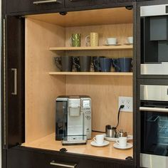 A hidden coffee bar (kitchen beverage center) with space for a coffee maker and other appliances, shelves for #coffee mugs and interior cabinet outlet for power featuring Dura Supreme #Cabinetry #gilmanskitchensandbaths
