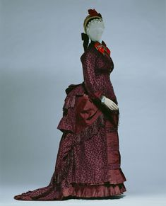 """Day Dress, Emile Pingat, Paris, France: ca. 1883, bodice, skirt and train of silk cut velvet, trimmed with fringe and chenille. """"...Wealthy American women were common patrons of Paris 'haute couture', a world in which Worth and Pangat, two designers, enjoyed popularity. These rich, American women periodically traveled to Paris, ordered clothes, and returned to the U.S. with many high class, haute couture creations."""" Label: """"E. PINGAT, 30 RUE LOUIS-LE-GRAND, PARIS"""""""
