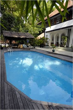 Just outside the living room's tall arched windows is a swimming pool and patio area. Best Interior Design, Interior Design Inspiration, Colonial Exterior, Modern Farmhouse Design, Arched Windows, Outdoor Living, Outdoor Decor, White Houses, Singapore