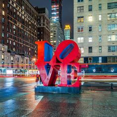 Robert Indiana's LOVE sculpture on Sixth Avenue at West 55th Street in Midtown Manhattan, New York City by Noel YC @nyclovesnyc - The Best Photos and Videos of New York City including the Statue of Liberty, Brooklyn Bridge, Central Park, Empire State Building, Chrysler Building and other popular New York places and attractions.