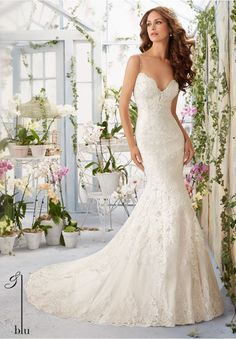 """Wedding Gowns By Blu featuring Scalloped Alencon Lace Edging Contours the Net Gown with Appliques and Crystal Beading Available in Three Lengths: 55"""", 58"""", 61"""". Colors available:White, Ivory, Ivory/Light Gold, Ivory/Blush."""