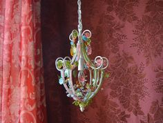 Petite Chandelier Lighting, Woodland Fairy  This magical little number is extra versatile in transparent shades of aqua, golden yellow, warm pink and spring green. Delicate and fairy-like, it boasts dozens of wired-on crystal and acrylic blossoms, leaves, butterflies and rhinestones on a beaded frame, creating a sparkling world within. Four leaded cut crystal teardrop prisms in different colors grace the top. Perfect for above a crib, in a reading corner, a powder room or dressing room, this…
