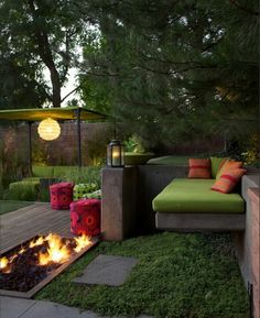 cool multi leveled outdoor lounge-y space. modern. fire pit. little grass. cool awning.