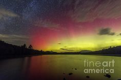 The Aurora Borealis lights up the sky and waters of Ricker Pond in Grafton State Forest in Ryegate VT, by John Vose.