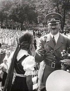Adolf Hitler giving a young girl a cheek squeezing, 1930's