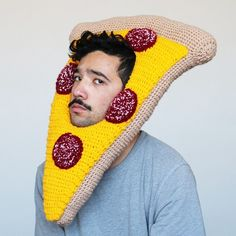 It's no secret that Melbourne-based artist Phil Ferguson is fond of food. After all, giant slices of crocheted pizza, cracked eggs, bacon, hot dogs, and much more are strapped onto the top or side of his head. They take the form of decorative hats and costumes that frame the wearer's face